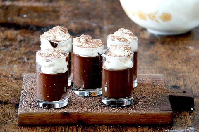 A board filled with small glasses filled with chocolate pots de creme and topped with homemade whipped cream and shaved chocolate over top.