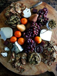 A cheese board filled with homemade three-seed crackers, cheese, candied pepitas, fruit, and quince paste.