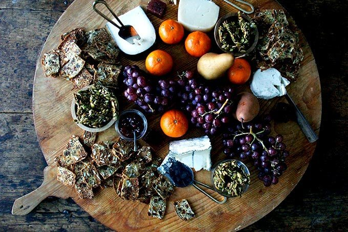 A cheese board loaded with homemade three-seed crackers, grapes, oranges, pears, and candied pepitas.