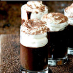 Chocolate pots de creme in small glasses topped with whipped cream on a board.