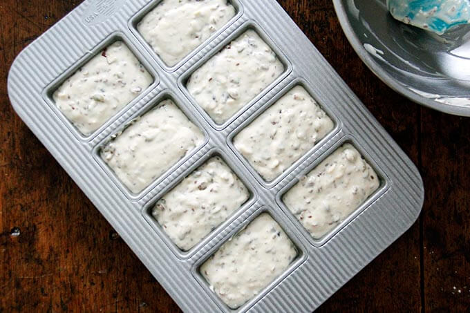 8-pan mini loaf pan filled with three seed cracker batter.