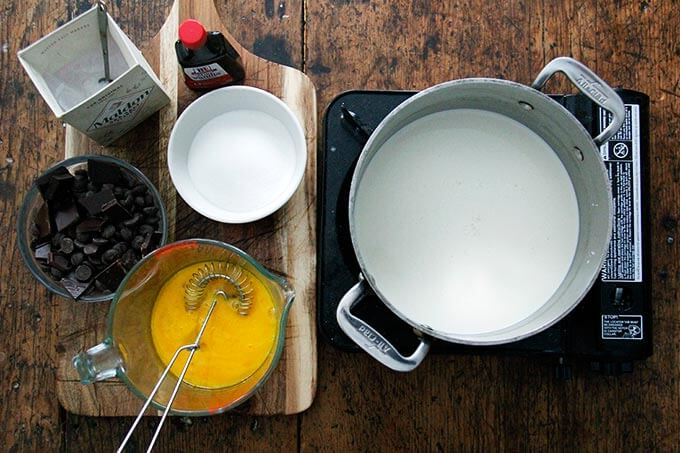 Overhead shot of a pot of cream on a portable burner aside other ingredients for stovetop pots de creme.