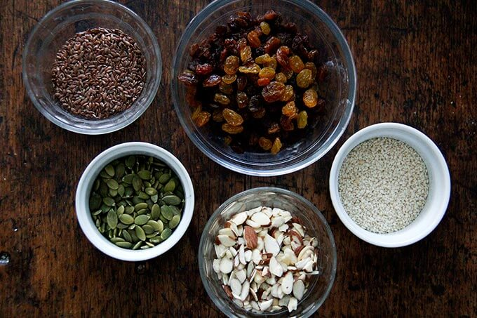 Three seeds, almonds, and golden raisins in a bowl.