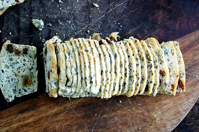 A loaf of three seed crackers sliced thinly.