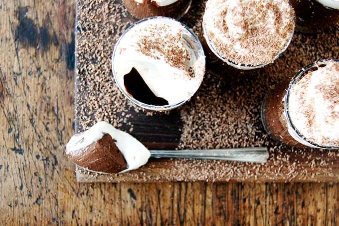 A board filled with small glasses filled with chocolate pots de creme and topped with homemade whipped cream, shaved chocolate, and a spoon.