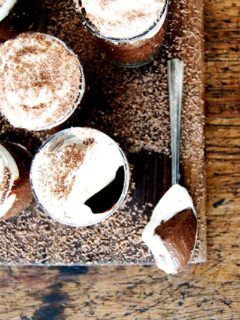 A board filled with small glasses filled with chocolate pot de creme and topped with homemade whipped cream.