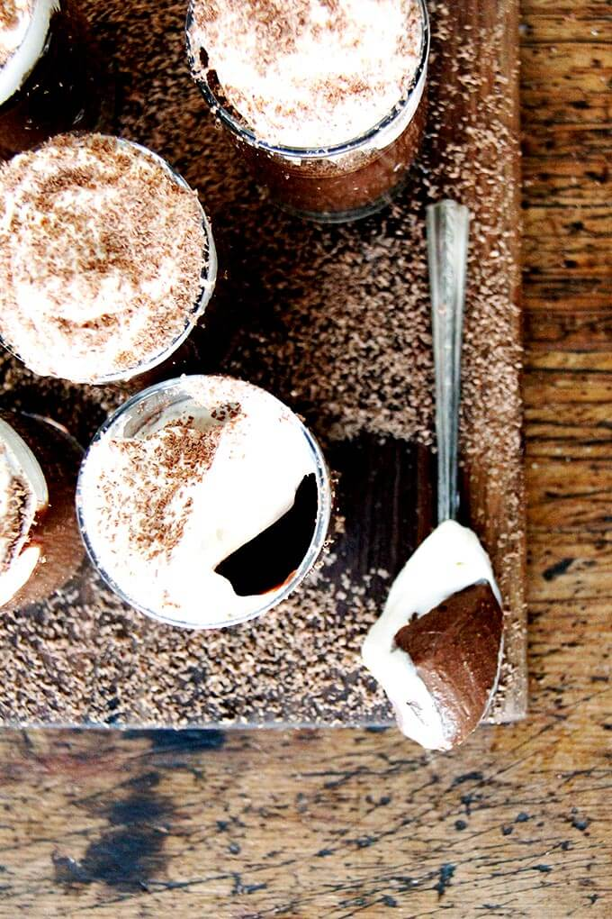 A board filled with small glasses filled with chocolate pots de creme and topped with homemade whipped cream.
