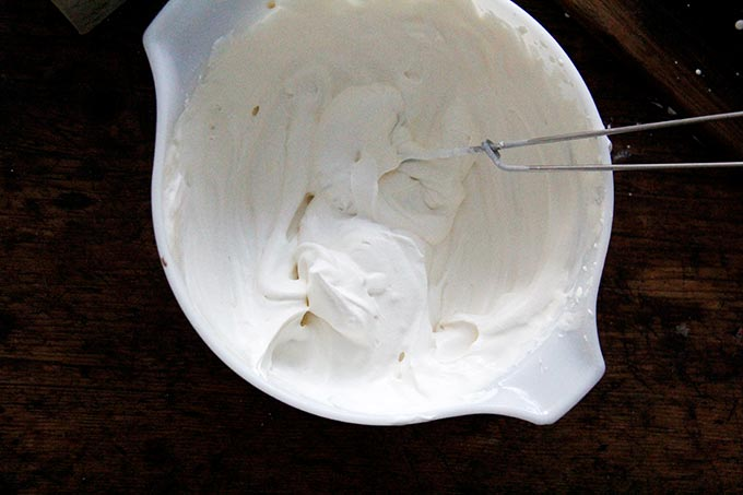 A large bowl filled with homemade whipped cream and a wire whip.