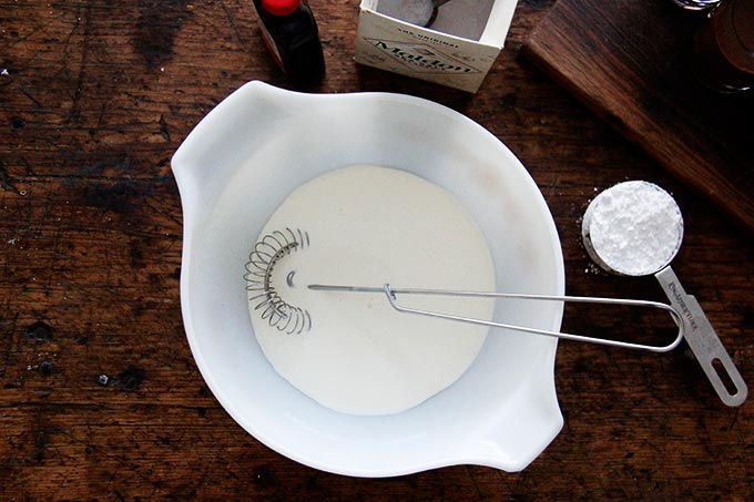 A large bowl filled with heavy cream and a wire whip.