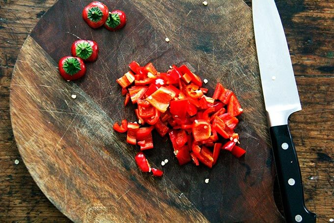 A cutting board with chopped hot chilies.