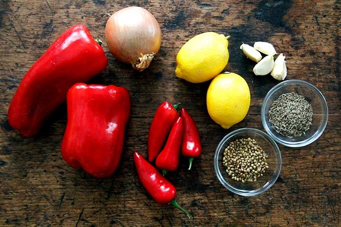 Ingredients for homemade harissa: peppers, onion, chilies, lemon, garlic, cumin, and coriander.