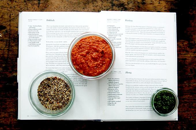 A cookbook open to the condiments page with recipes for harissa, dukkah, and skhug.