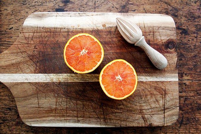 A halved orange on a board.