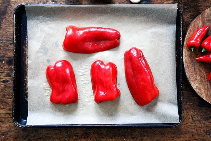 A parchment-lined sheet pan with halved bell peppers.