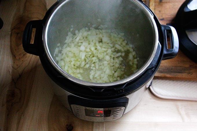 An overhead shot of an Instant Pot sautéing an onion.