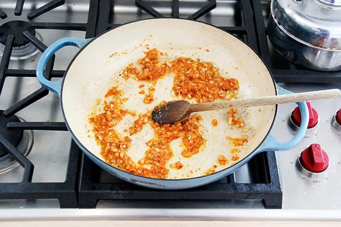 A skillet with harissa rice ingredients all stirred together.
