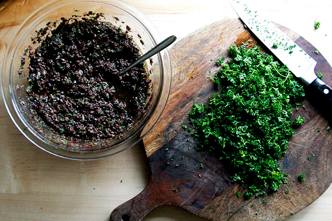 A bowl of black olive tapenade aside a chopping board with chopped parsley and a chef's knife.