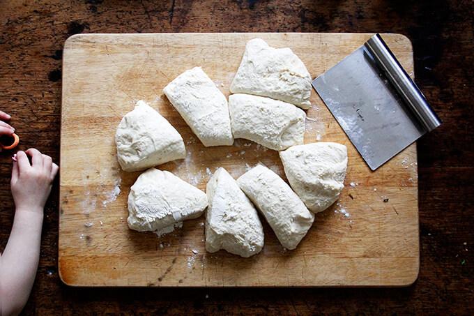 Brioche dough on a board portioned into 8 pieces.