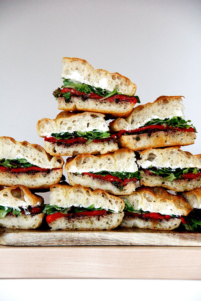 A stack of sandwiches with black olive tapenade, roasted red peppers, whipped honey goat cheese, and lettuce.