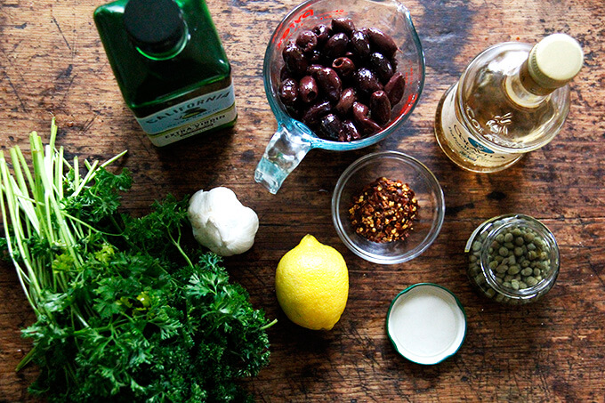 An overhead shot of the ingredients to make black olive tapenade.
