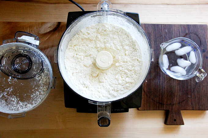 A counter with a food processor filled with dry ingredients pulsed with butter.
