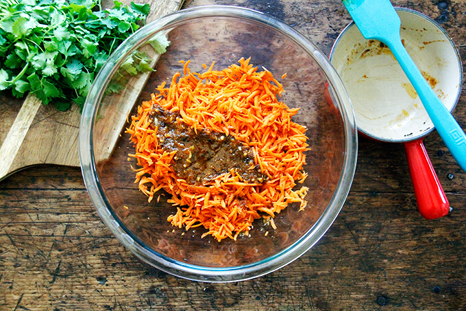 A large bowl filled with grated carrots and warm harissa dressing.