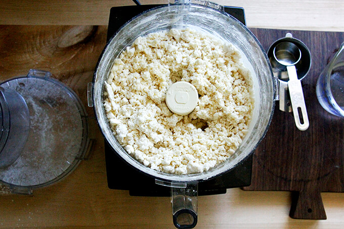 A counter with a food processor filled with dry ingredients pulsed with butter and ice water.