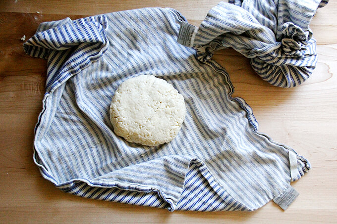 A tea towel with a round of food processor pastry dough.