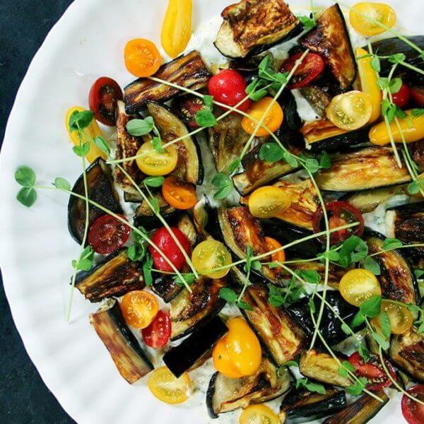 Roasted eggplant salad on a platter with tzatziki and tomatoes.