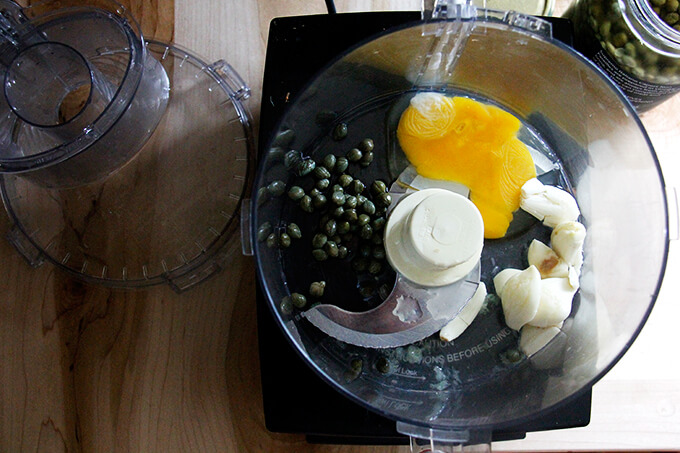 A food processor with ingredients to make classic aioli.