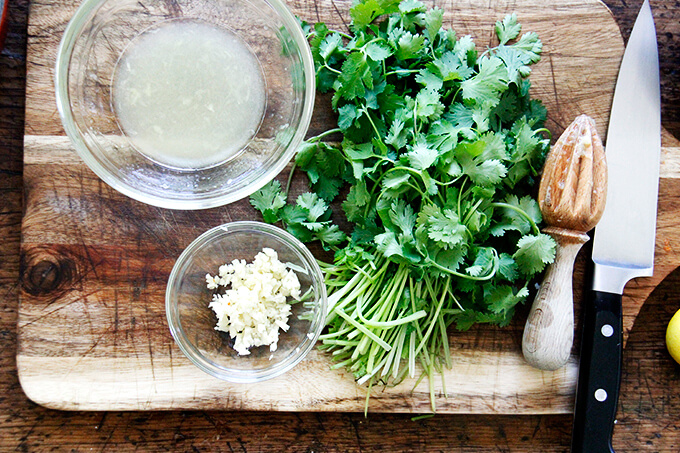 A board with minced garlic, lemon, and cilantro.