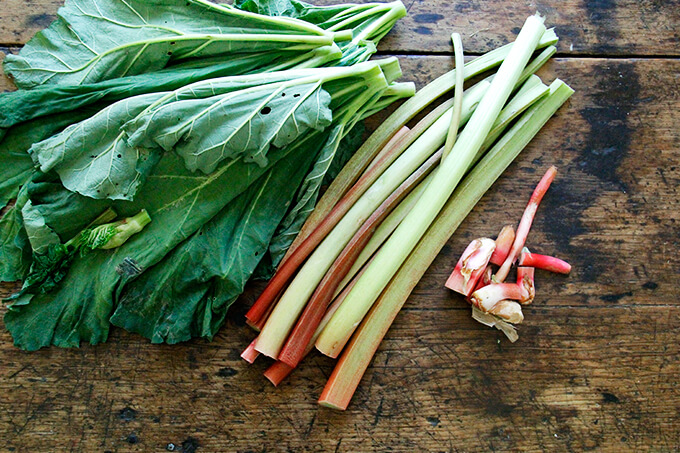 A board with rhubarb and rhubarb leaves.