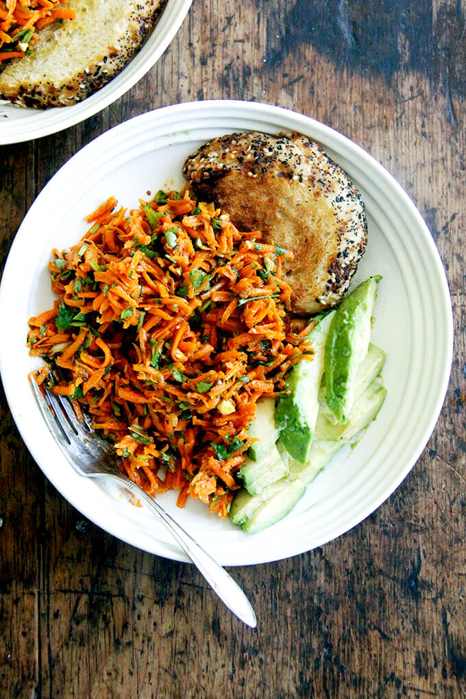 A bowl of Moroccan carrot salad aside bread and avocado.