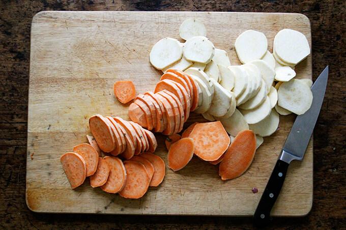 Sliced sweet potatoes on a board.