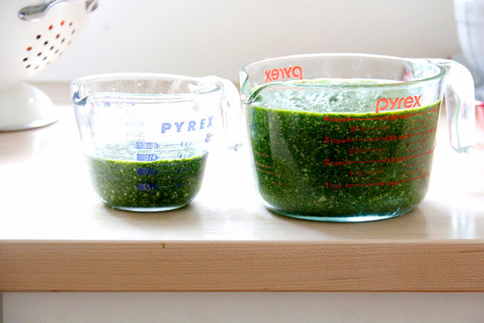 Two pyrex liquid measures filled with basil pesto.