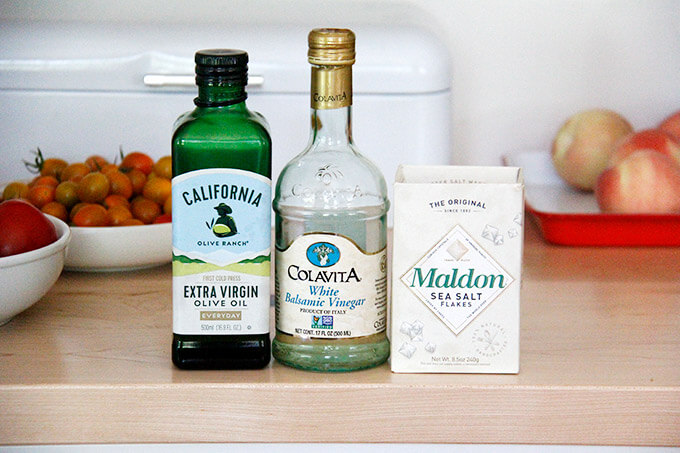 The dressing ingredients on a board: colavita white balsamic, california olive ranch olive oil, maldon sea salt.