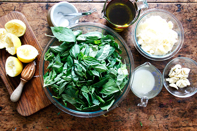 A table with pesto ingredients: basil, lemon, salt, olive oil, parmesam, garlic.