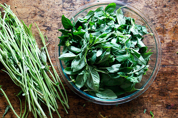 A bowl of basil leaves aside stems on a table.