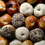 A sheet pan filled with freshly baked bagels.