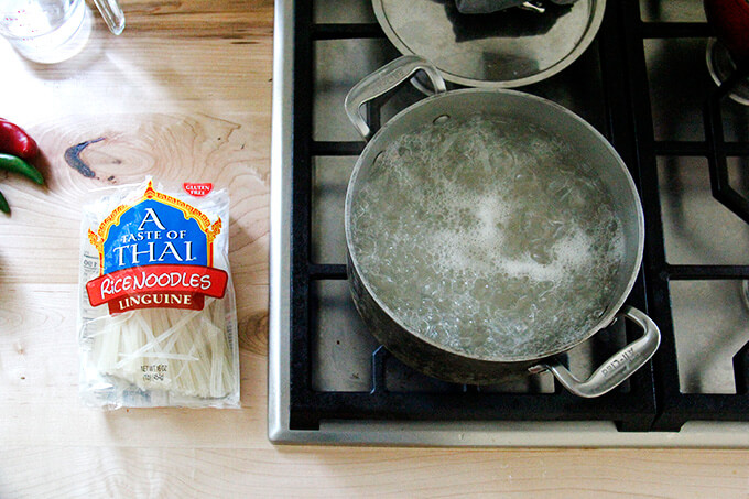 A stovetop with a pot of boiling water aside a package of rice noodles.