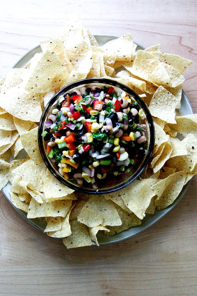 A bowl of Texas Caviar aside tortilla chips.