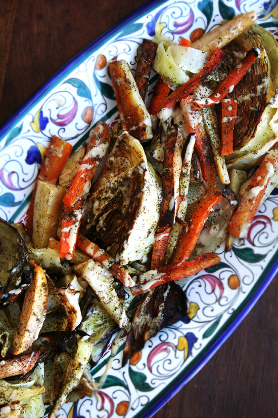 A platter of roasted vegetables with tahini sauce.