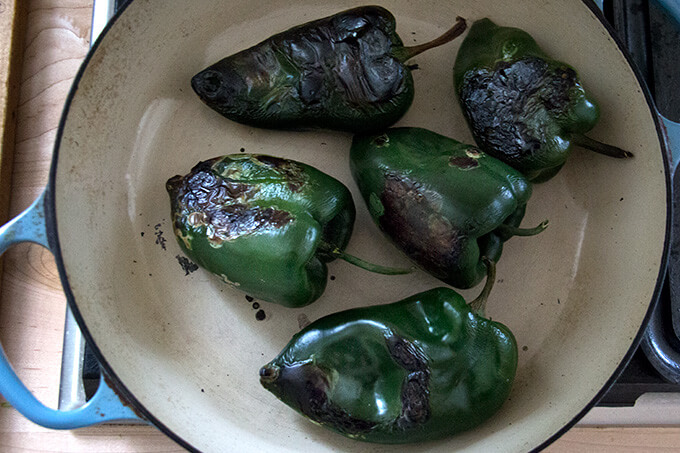 Blistered poblano peppers in a skillet.