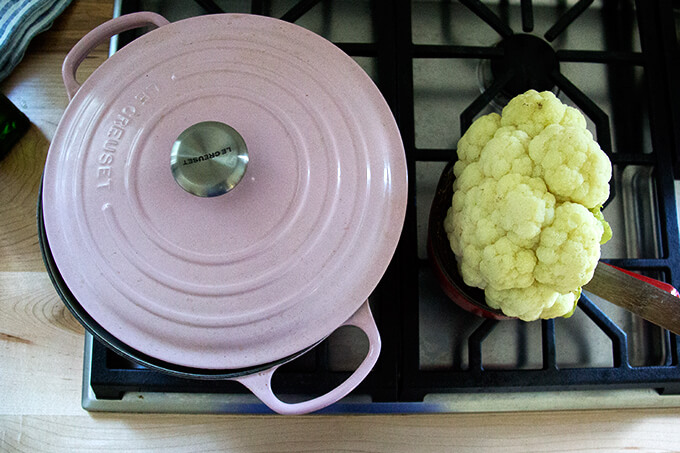 An overhead shot of a Le Creuset Dutch oven aside a head of poached cauliflower.