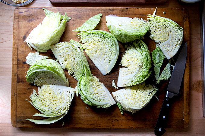 A board with a head of Savoy cabbage cut into wedges.