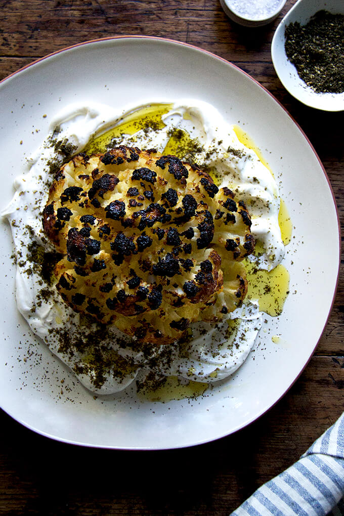 A an overhead shot of a plate of whole roasted cauliflower with lemony yogurt sauce.