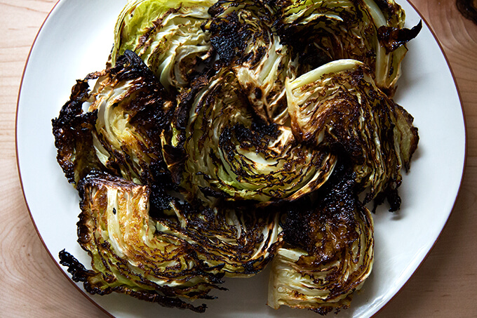 A platter with roasted cabbage wedges on top.