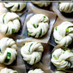 A board with 12 shaped Chinese scallion buns, each on a square of parchment paper.