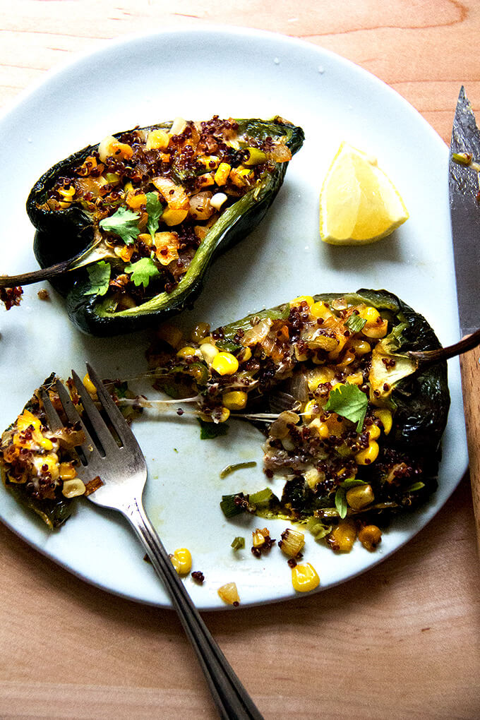 A pan of blistered poblano peppers stuffed with quinoa, corn, and Monterey Jack on a plate.