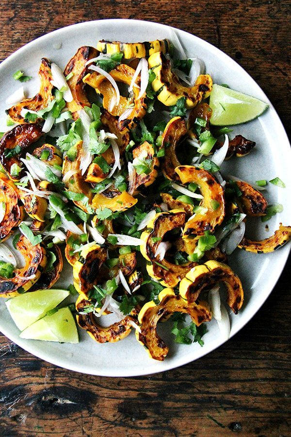 A plate of roasted delicata squash with shallots, chilies, and lime.